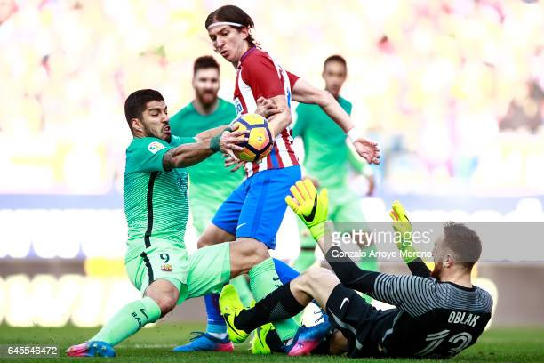 Luis Suarez of FC Barcelona handles the ball in front of goalkeeper Jan Oblak of Atletico de Madrid and his teammate Filipe Luis during the La Liga...