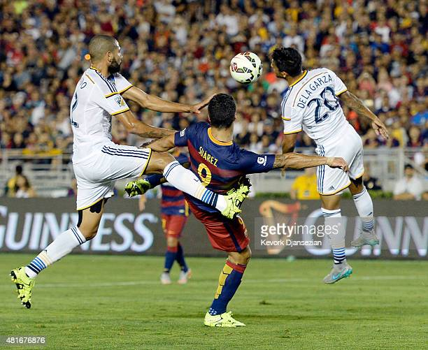 Luis Suarez of FC Barcelona is kicked in the back by Leonardo of Los Angeles Galaxy as AJ DeLaGarza heads the ball away during the first half of...