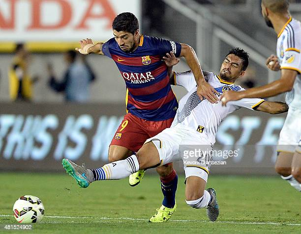 Luis Suarez of FC Barcelona is tackled by AJ DeLaGarza of Los Angeles Galaxy during the first half of International Champions Cup friendly soccer...