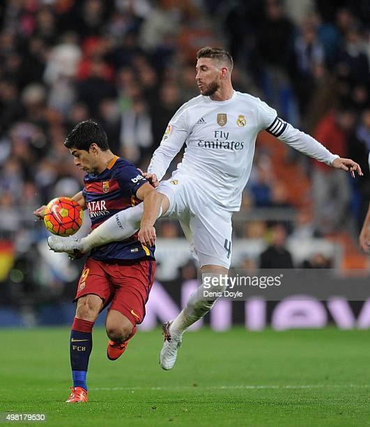 Luis Suarez of FC Barcelona is tackled by Sergio Ramos of Real Madrid during the La Liga match between Real Madrid and Barcelona at Estadio Santiago...