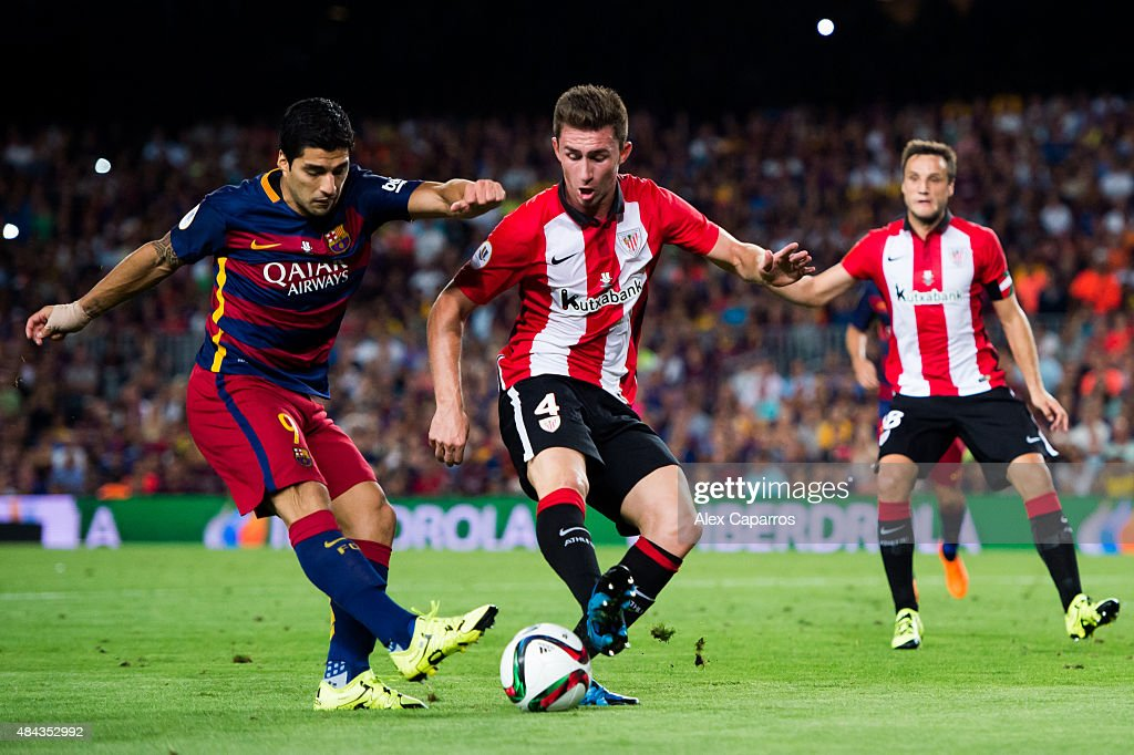 Luis Suarez (L) of FC Barcelona kicks the ball next to <a gi-track='captionPersonalityLinkClicked' href=/galleries/search?phrase=Aymeric+Laporte&family=editorial&specificpeople=7894319 ng-click='$event.stopPropagation()'>Aymeric Laporte</a> (C) of Athletic Club during the Spanish Super Cup second leg match between FC Barcelona and Athletic Club at Camp Nou on August 17, 2015 in Barcelona, Spain.
