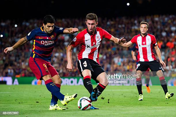 Luis Suarez of FC Barcelona kicks the ball next to Aymeric Laporte of Athletic Club during the Spanish Super Cup second leg match between FC...