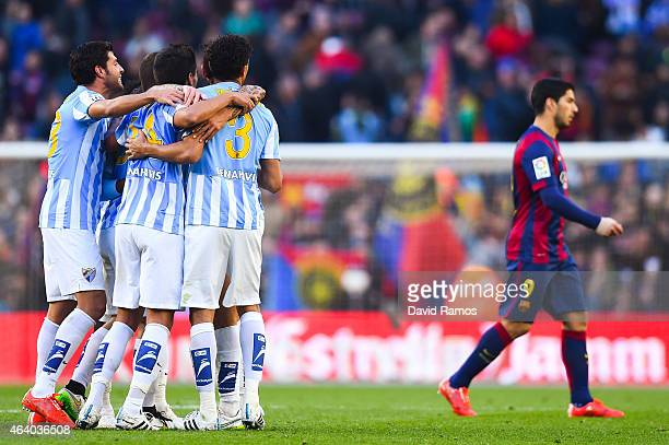Luis Suarez of FC Barcelona leaves the pitch as Malaga CF players celebrate the victory at the end of the La Liga match between FC Barcelona and...