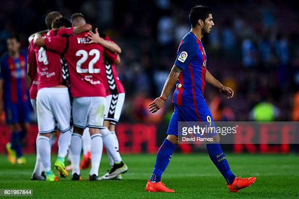 Luis Suarez of FC Barcelona leaves the pitch dejected as Deportivo Alaves players celebrate victory at the end of the La Liga match between FC...