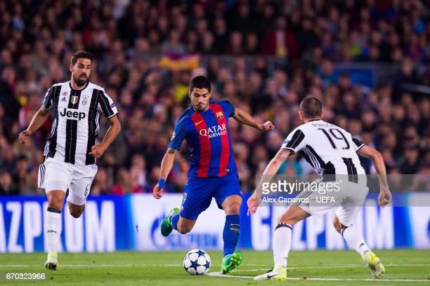 Luis Suarez of FC Barcelona plays the ball between Sami Khedira and Leonardo Bonucci of Juventus during the UEFA Champions League Quarter Final...