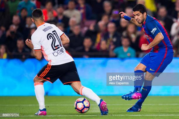 Luis Suarez of FC Barcelona plays the ball past Martin Montoya of Valencia CF during the La Liga match between FC Barcelona and Valencia CF at Camp...