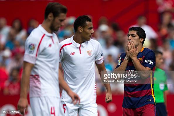 Luis Suarez of FC Barcelona reacts as he fails to score behind Timothee Kolodziejczak of Sevilla FC and his teammate Grzegorz Krychowiak during the...