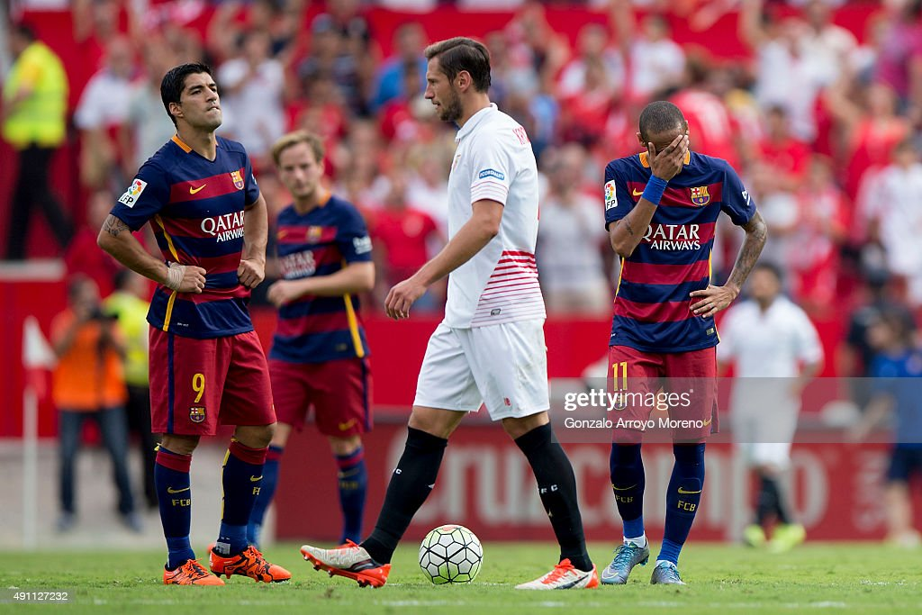 Luis Suarez (L) of FC Barcelona reacts with teammate Neymar JR. (R) as Sevilla FC palyers celebrate their first goal during the La Liga match between Sevilla FC and FC Barcelona at Estadio Ramon Sanchez Pizjuan on October 3, 2015 in Seville, Spain.