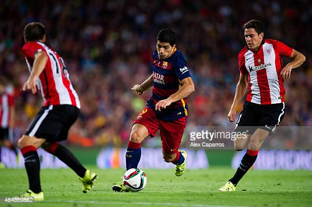Luis Suarez of FC Barcelona runs with the ball between Carlos Gurpegi and Gorka Elustondo of Athletic Club during the Spanish Super Cup second leg...