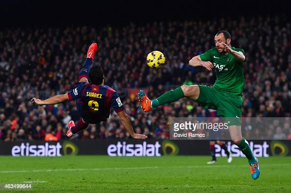 Luis Suarez of FC Barcelona scores his team's fifth goal under a challenge by Ivan Ramis of Levante UD during the La Liga match between FC Barcelona...