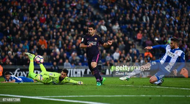 Luis Suarez of FC Barcelona scores his team's third goal past Diego Lopez and David Lopez of RCD Espanyol during the La Liga match between RCD...