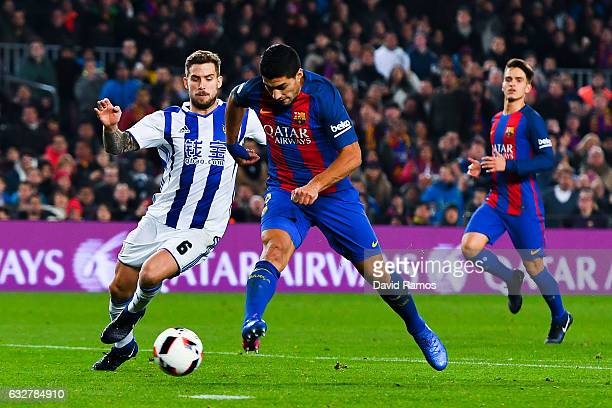 Luis Suarez of FC Barcelona scores his team's third goal past Inigo Martinez of Real Sociedad de Futbol during the Copa del Rey quarterfinal second...