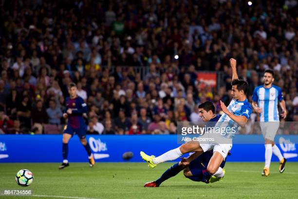 Luis Suarez of FC Barcelona shoots the ball under pressure from Luis Hernandez of Malaga CF during the La Liga match between Barcelona and Malaga at...