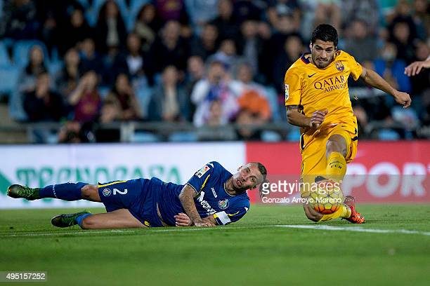 Luis Suarez of FC Barcelona strikes the ball ahead of Alexis Ruano of Getafe CF during the La Liga match between Getafe CF and FC Barcelona at...