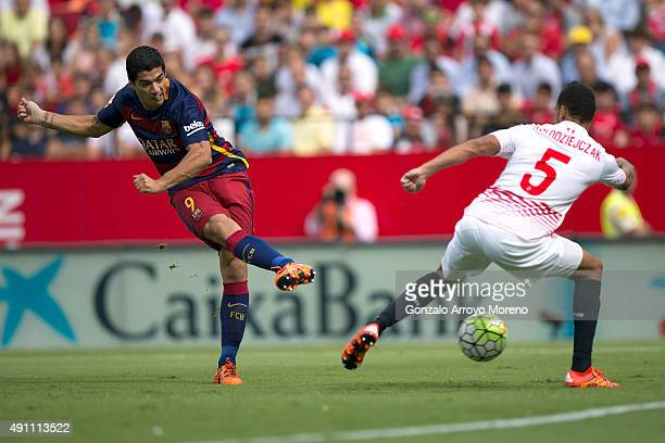 Luis Suarez of FC Barcelona strikes the ball over Timothee Kolodziejczak of Sevilla FC during the La Liga match between Sevilla FC and FC Barcelona...