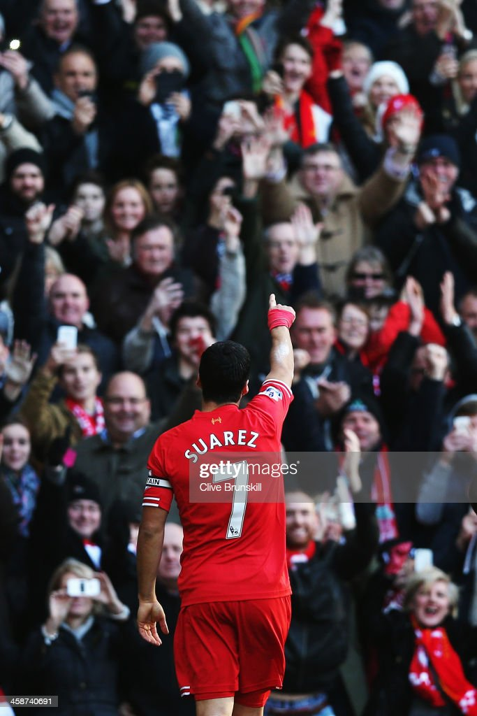 Luis Suarez of Liverpool acknowledges his sides fans after scoring during the Barclays Premier League match between Liverpool and Cardiff City at Anfield on December 21, 2013 in Liverpool, England.