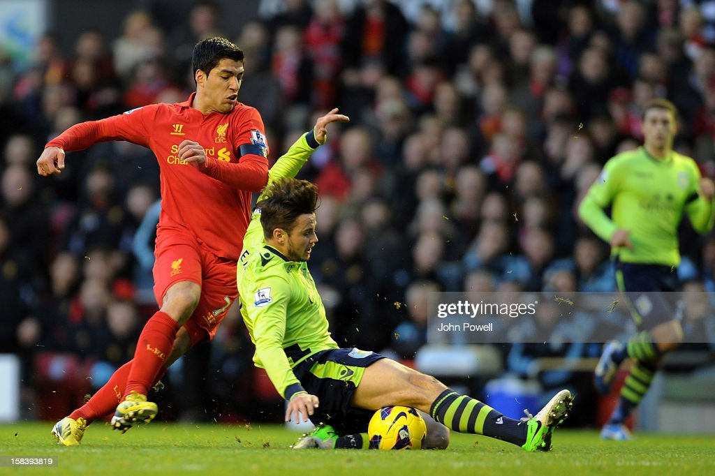 Luis Suarez of Liverpool and Chris Herd of Aston Villa compete during the Barclays Premier League match between Liverpool and Aston Villa at Anfield on December 15, 2012 in Liverpool, England.