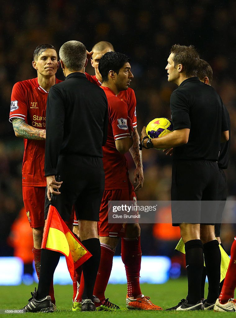 Luis Suarez of Liverpool argues with Referee Craig Pawson at the end of the match during the Barclays Premier League match between Liverpool and Hull City at Anfield on January 1, 2014 in Liverpool, England.