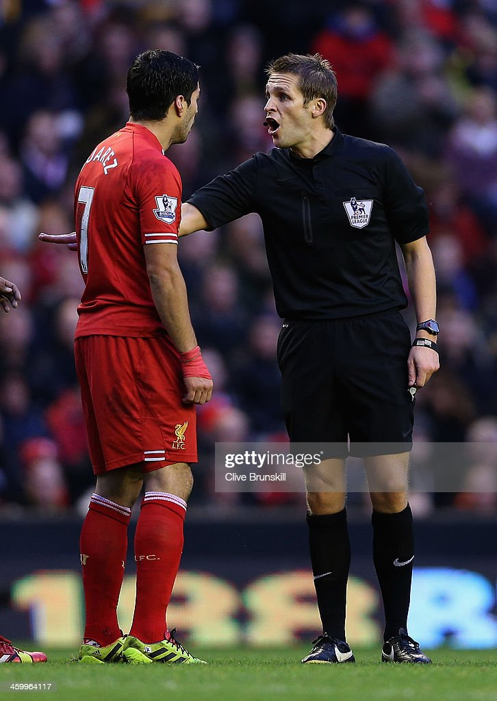 Luis Suarez of Liverpool argues with referee Mr C Pawson during the Barclays Premier League match between Liverpool and Hull City at Anfield on January 1, 2014 in Liverpool, England.