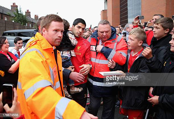 Luis Suarez of Liverpool arrives at Anfield carrying his daughter Delfina prior to the Barclays Premier League match between Liverpool and Stoke City...