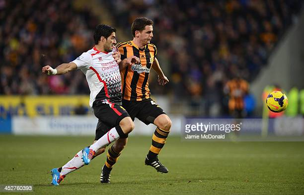 Luis Suarez of Liverpool battles for the ball with Alex Bruce of Hull City during the Barclays Premier League match between Hull City and Liverpool...