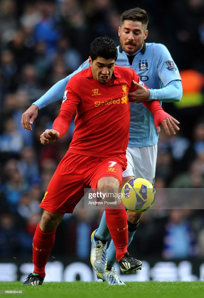 Luis Suarez of Liverpool battles with Javi Garcia of Manchester City during the Barclays Premier League match between Manchester City and Liverpool at Etihad Stadium on February 3, 2013 in Manchester, England.