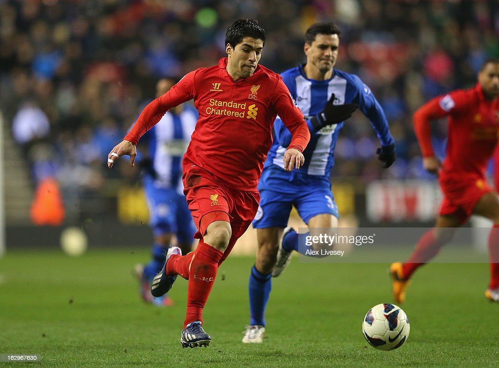 Luis Suarez of Liverpool breaks past <a gi-track='captionPersonalityLinkClicked' href=/galleries/search?phrase=Paul+Scharner&family=editorial&specificpeople=620484 ng-click='$event.stopPropagation()'>Paul Scharner</a> of Wigan Athletic on his way to scoring his third goal during the Barclays Premier League match between Wigan Athletic and Liverpool at the DW Stadium on March 2, 2013 in Wigan, England.