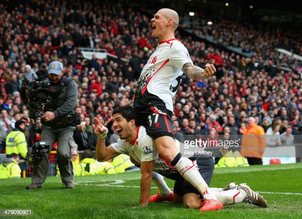 Luis Suarez of Liverpool celebrates scoring his team's third goal with Martin Skrtel during the Barclays Premier League match between Manchester...