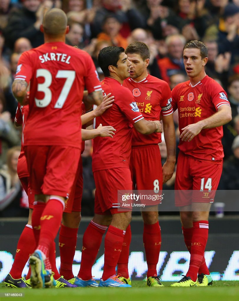 Luis Suarez of Liverpool celebrates scoring the opening goal with his team-mates during the Barclays Premier League match between Liverpool and Fulham at Anfield on November 9, 2013 in Liverpool, England.