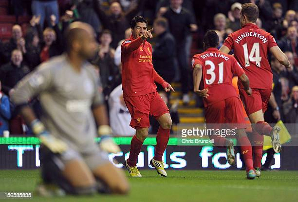 Luis Suarez of Liverpool celebrates scoring the opening goal with teammates Raheem Sterling and Jordan Henderson as Ali Al Habsi of Wigan Athletic...