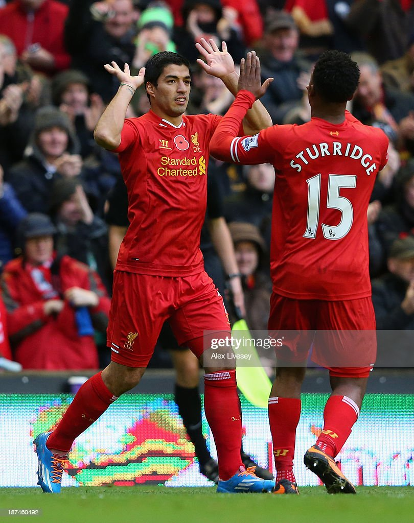 Luis Suarez of Liverpool celebrates scoring the third goal with his team-mate <a gi-track='captionPersonalityLinkClicked' href=/galleries/search?phrase=Daniel+Sturridge+-+Soccer+Player&family=editorial&specificpeople=677270 ng-click='$event.stopPropagation()'>Daniel Sturridge</a> during the Barclays Premier League match between Liverpool and Fulham at Anfield on November 9, 2013 in Liverpool, England.
