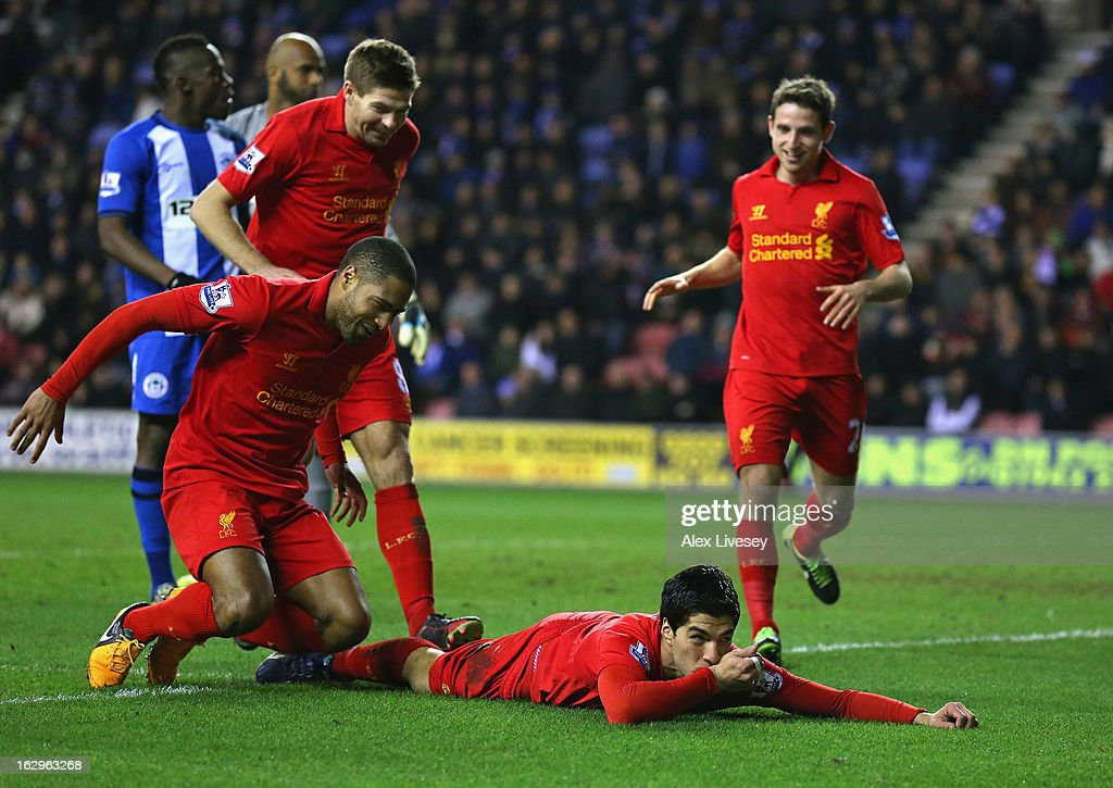 Luis Suarez of Liverpool celebrates with <a gi-track='captionPersonalityLinkClicked' href=/galleries/search?phrase=Glen+Johnson&family=editorial&specificpeople=209192 ng-click='$event.stopPropagation()'>Glen Johnson</a> and <a gi-track='captionPersonalityLinkClicked' href=/galleries/search?phrase=Steven+Gerrard&family=editorial&specificpeople=202052 ng-click='$event.stopPropagation()'>Steven Gerrard</a> after scoring his third goal to complete a hat trick during the Barclays Premier League match between Wigan Athletic and Liverpool at the DW Stadium on March 2, 2013 in Wigan, England.