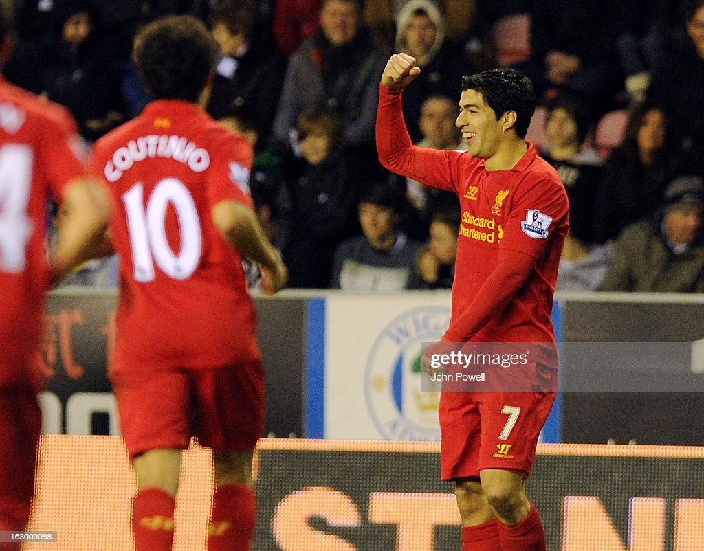 Luis Suarez of Liverpool celebrates with his team-mates after scoring the third for his club during the Barclays Premier League match between Wigan Athletic and Liverpool at DW Stadium on March 2, 2013 in Wigan, England.