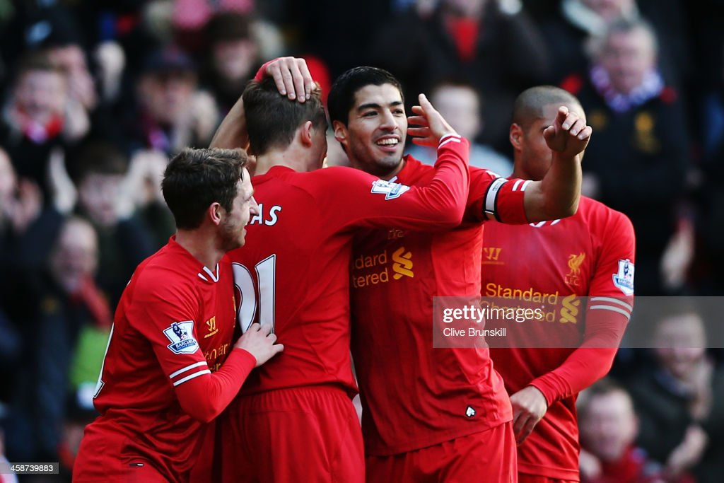 Luis Suarez (2nd right) of Liverpool celebrates with team mates after scoring during the Barclays Premier League match between Liverpool and Cardiff City at Anfield on December 21, 2013 in Liverpool, England.