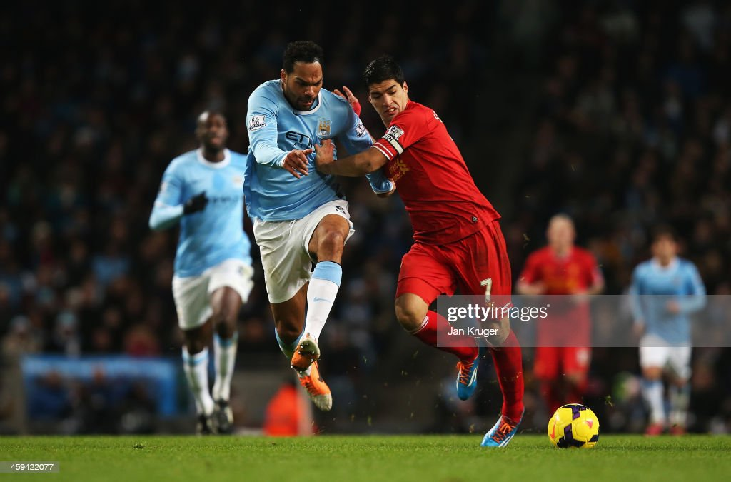 Luis Suarez of Liverpool challenges for the ball with <a gi-track='captionPersonalityLinkClicked' href=/galleries/search?phrase=Joleon+Lescott&family=editorial&specificpeople=687246 ng-click='$event.stopPropagation()'>Joleon Lescott</a> of Manchester City during the Barclays Premier League match between Manchester City and Liverpool at Etihad Stadium on December 26, 2013 in Manchester, England.
