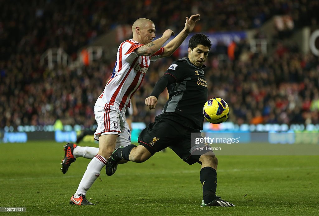 Luis Suarez of Liverpool competes with Andy Wilkinson of Stoke City during the Barclays Premier League match between Stoke City and Liverpool at the Britannia Stadium on December 26, 2012, in Stoke-on-Trent, England.