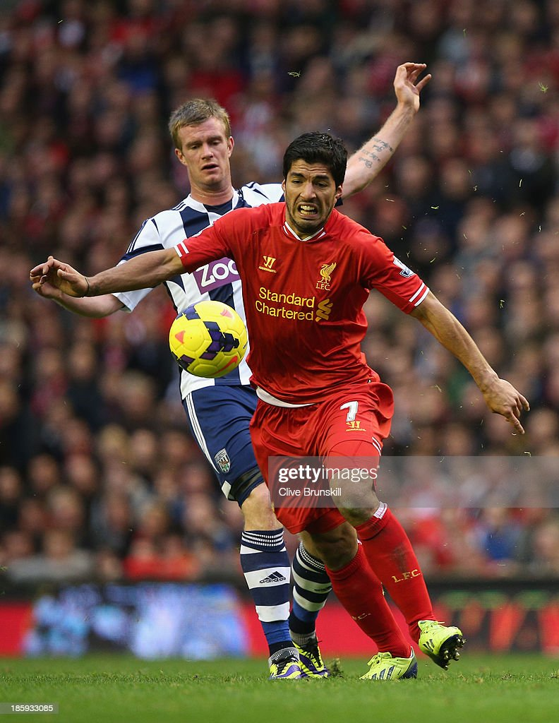 Luis Suarez of Liverpool competes with Chris Brunt of West Bromwich Albion during the Barclays Premier League match between Liverpool and West Bromwich Albion at Anfield on October 26, 2013 in Liverpool, England.