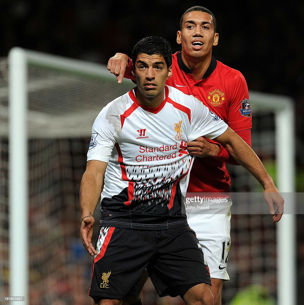 Luis Suarez of Liverpool competes with Chris Smalling of Manchester United during the Capital One Cup Third Round match between Manchester United and Liverpool at Old Trafford on September 25, 2013 in Manchester, England.