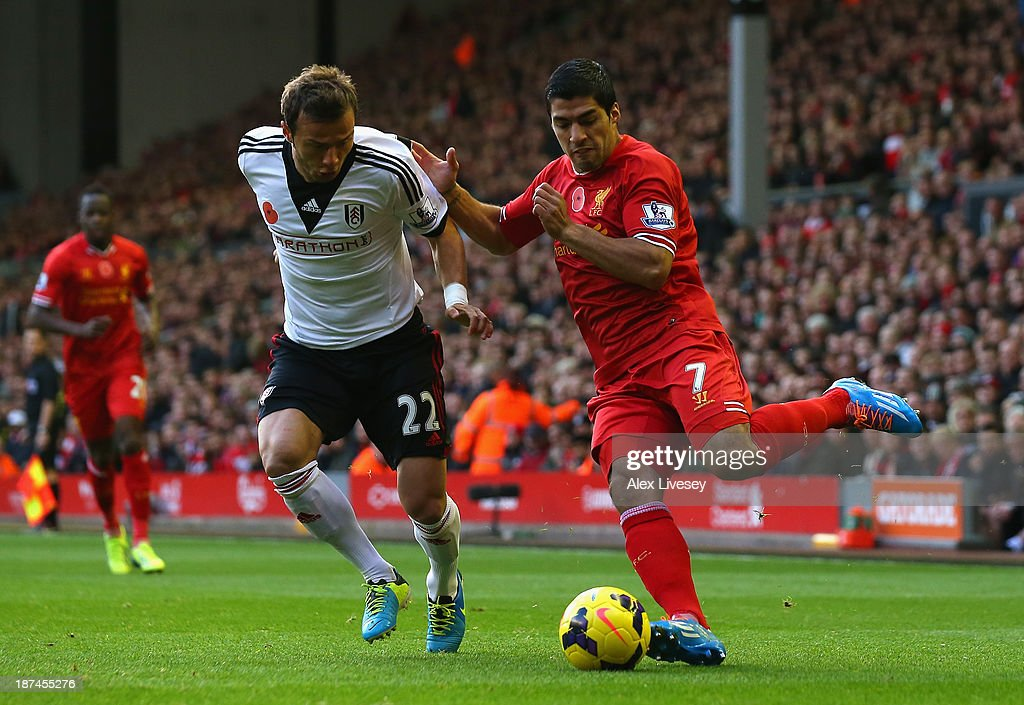 Luis Suarez of Liverpool competes with Elsad Zverotic of Fulham during the Barclays Premier League match between Liverpool and Fulham at Anfield on November 9, 2013 in Liverpool, England.