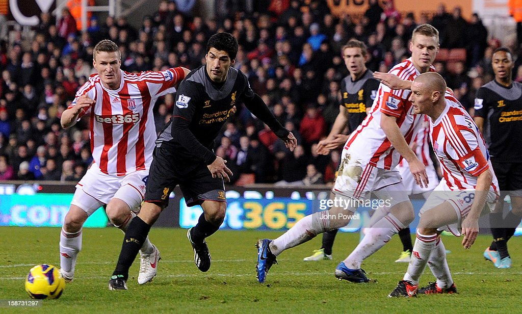 Luis Suarez of Liverpool competes with Robert Huth off Stoke City during the Barclays Premier League match between Stoke City and Liverpool at Britannia Stadium on December 26, 2012 in Stoke on Trent, England.