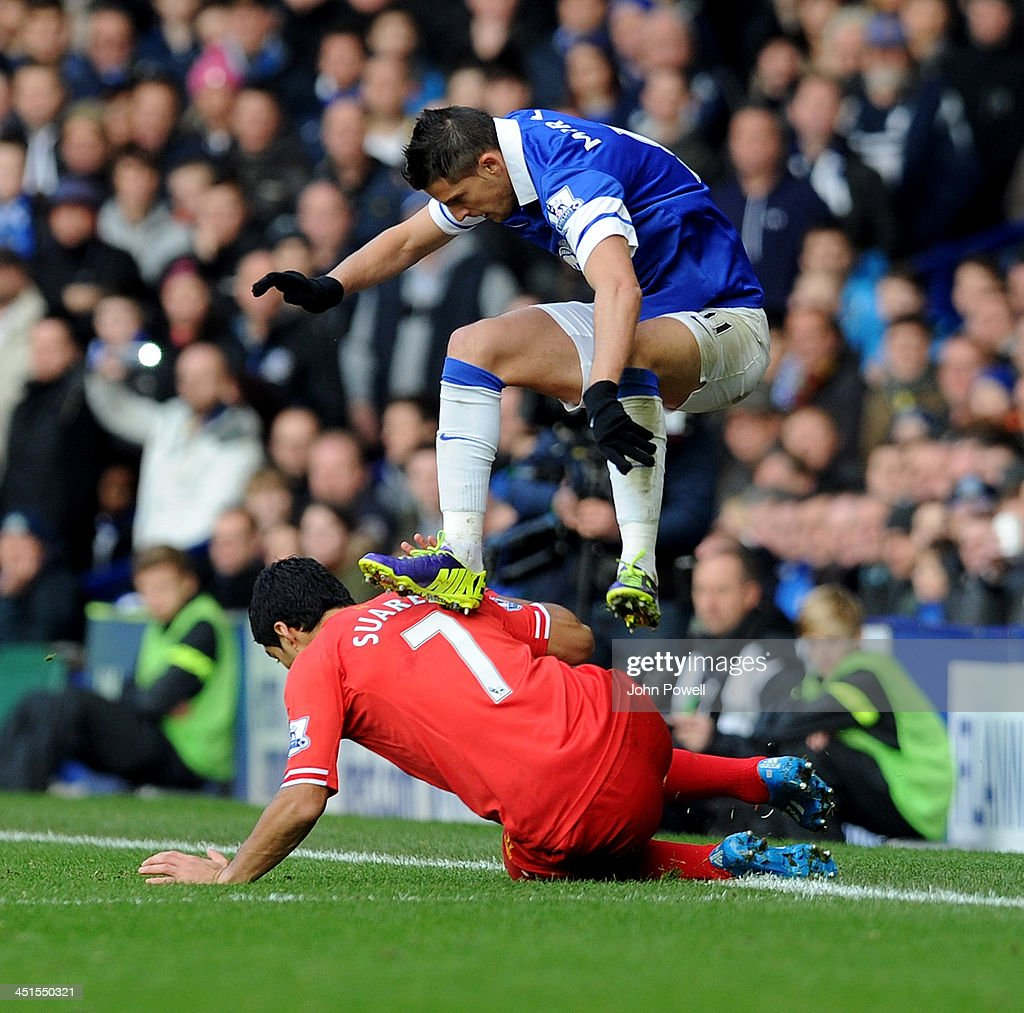 Luis Suarez of Liverpool gets stamped on by Kevin Mirallas of Everton during the Barclays Premier League match between Everton and Liverpool at Goodison Park on November 23, 2013 in Liverpool, England.