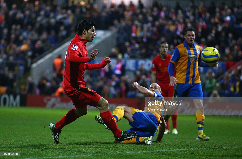 Luis Suarez of Liverpool goes around Alan Marriott of Mansfield Town to score during the FA Cup with Budweiser Third Round match between Mansfield Town and Liverpool at One Call Stadium on January 6, 2013 in Mansfield, England.