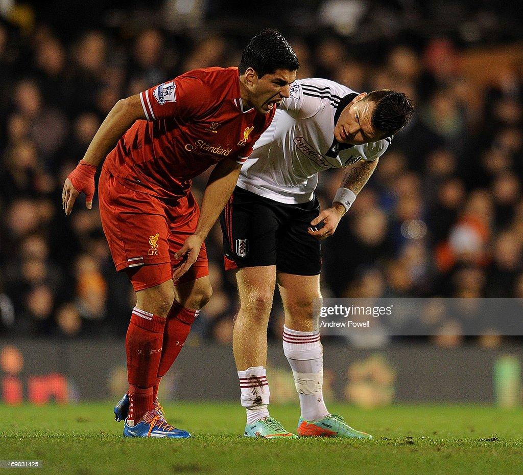 Luis Suarez of Liverpool helped up after a foul by <a gi-track='captionPersonalityLinkClicked' href=/galleries/search?phrase=John+Arne+Riise&family=editorial&specificpeople=204354 ng-click='$event.stopPropagation()'>John Arne Riise</a> of Fulham during the Barclays Premier Leauge match between Fulham and Liverpool at Craven Cottage on February 12, 2014 in London, England.