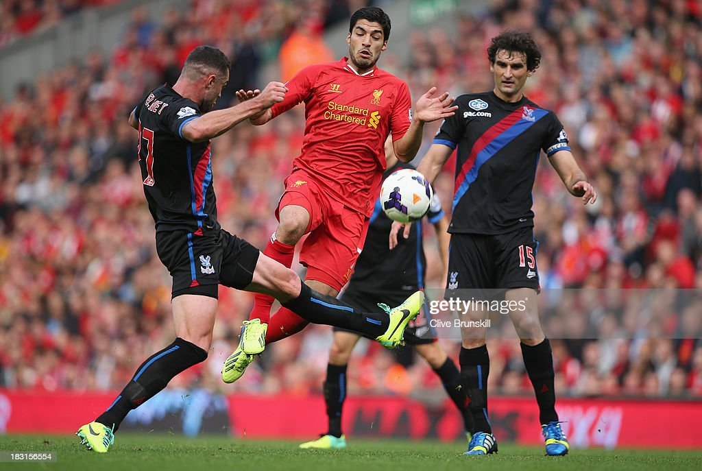 Luis Suarez of Liverpool in action with Damien Delaney and <a gi-track='captionPersonalityLinkClicked' href=/galleries/search?phrase=Mile+Jedinak&family=editorial&specificpeople=3123629 ng-click='$event.stopPropagation()'>Mile Jedinak</a> of Crystal Palace during the Barclays Premier League match between Liverpool and Crystal Palace at Anfield on October 5, 2013 in Liverpool, England.