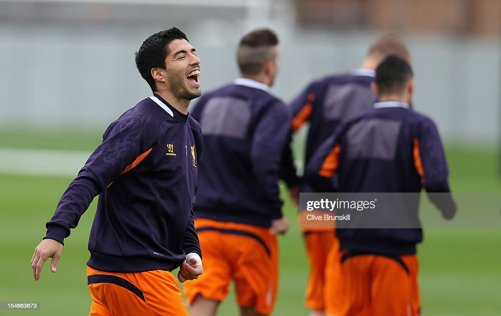 Luis Suarez of Liverpool in good spirits during a training session ahead of their UEFA Europa League group match against FC Anzhi Makhachkala at Melwood Training Ground on October 24, 2012 in Liverpool, England.