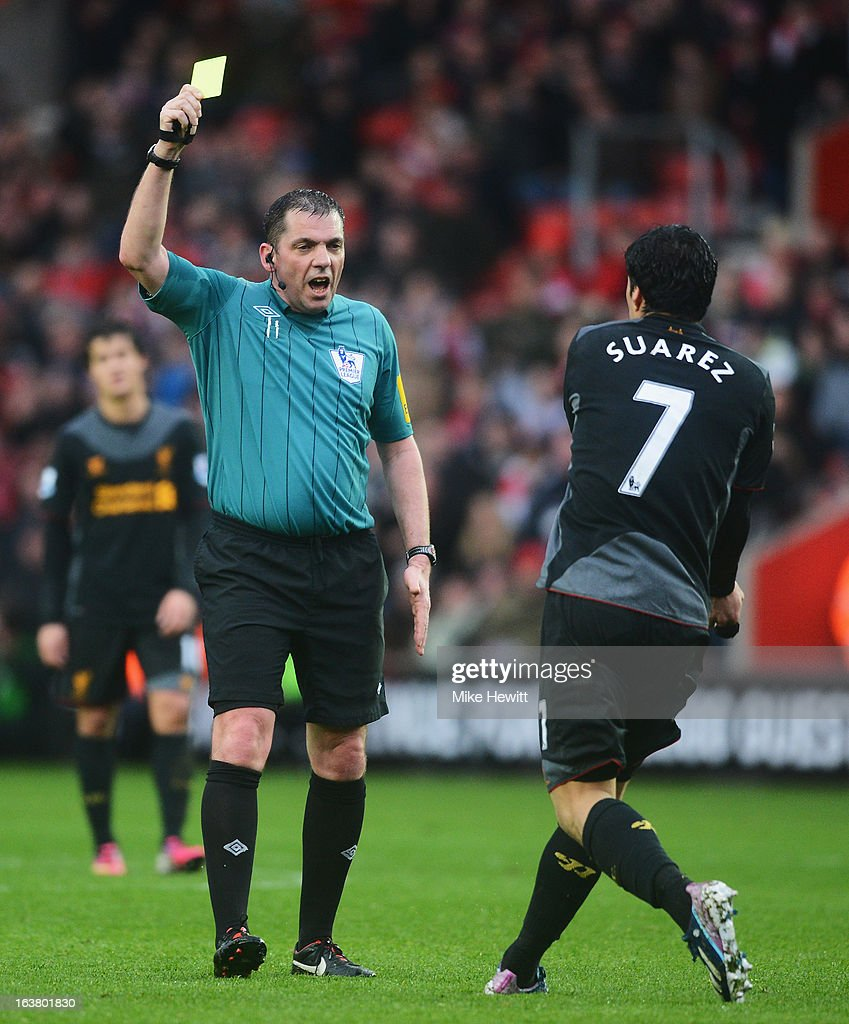 Luis Suarez of Liverpool is booked by referee Phil Dowd during the Barclays Premier League match between Southampton and Liverpool at St Mary's Stadium on March 16, 2013 in Southampton, England.