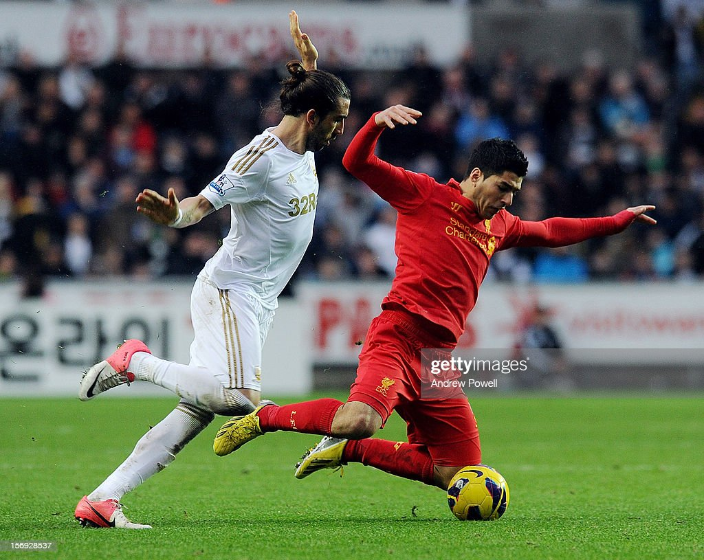 Luis Suarez of Liverpool is brought down by Chico Flores of Swansea City during the Barclays Premier League match between Swansea City and Liverpool at Liberty Stadium on November 25, 2012 in Swansea, Wales.