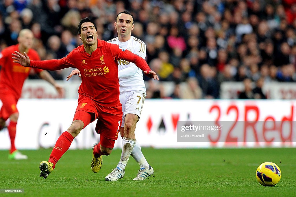 Luis Suarez of Liverpool is brought down by Leon Britton of Swansea City during the Barclays Premier League match between Swansea City and Liverpool at Liberty Stadium on November 25, 2012 in Swansea, Wales.
