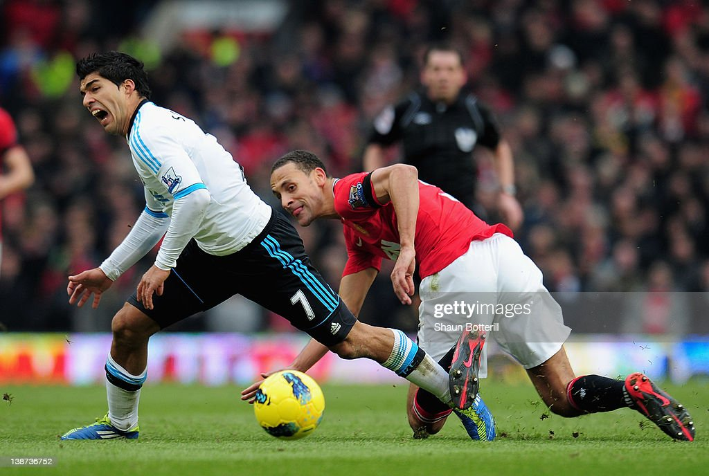 Luis Suarez of Liverpool is challenged by <a gi-track='captionPersonalityLinkClicked' href=/galleries/search?phrase=Rio+Ferdinand&family=editorial&specificpeople=157538 ng-click='$event.stopPropagation()'>Rio Ferdinand</a> of Manchester United during the Barclays Premier League match between Manchester United and Liverpool at Old Trafford on February 11, 2012 in Manchester, England.