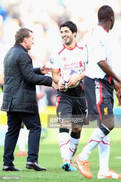 Luis Suarez of Liverpool is congratulated by his manager Brendan Rodgers at the final whistle after scoring a hat trick during his teams 63 victory...